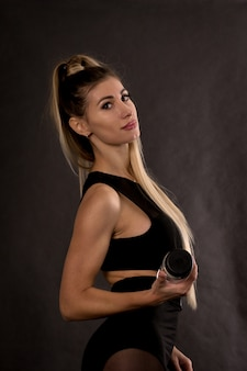 Jolie femme de remise en forme sur fond noir, corps féminin formé, mode de vie portrait, modèle caucasien, fitness girl s'entraîne avec haltère,
