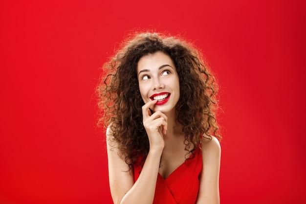 Jolie femme rêveuse charismatique et tendre avec une coiffure frisée en robe rouge mordant le doigt et souriant...
