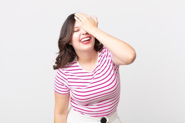 Jolie femme riant et giflant le front comme pour dire dã¢â€â™oh! j'ai oublié ou c'était une erreur stupide