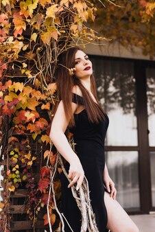 Jolie femme riche sexy dans une robe noire posant dans le parc, profitant d'une vie riche