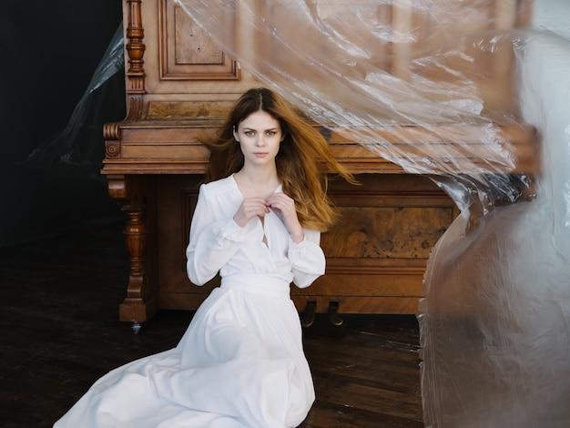 Jolie femme en robe blanche instrument de musique intérieur piano posant