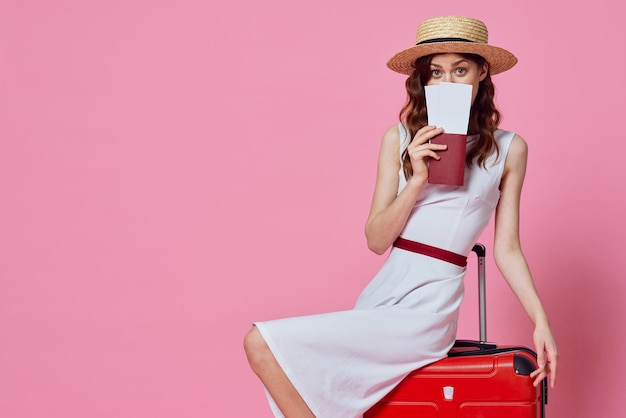 Jolie femme en robe blanche portant chapeau valise rouge passeports billets d'avion fond rose