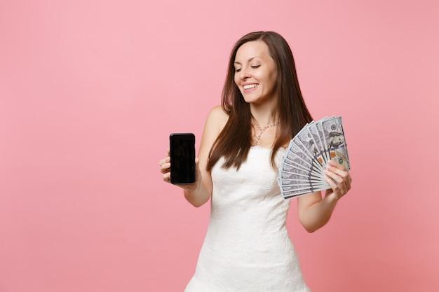 Jolie femme en robe blanche tenant un paquet de dollars, de l'argent en espèces, un téléphone portable avec un écran vide noir vierge