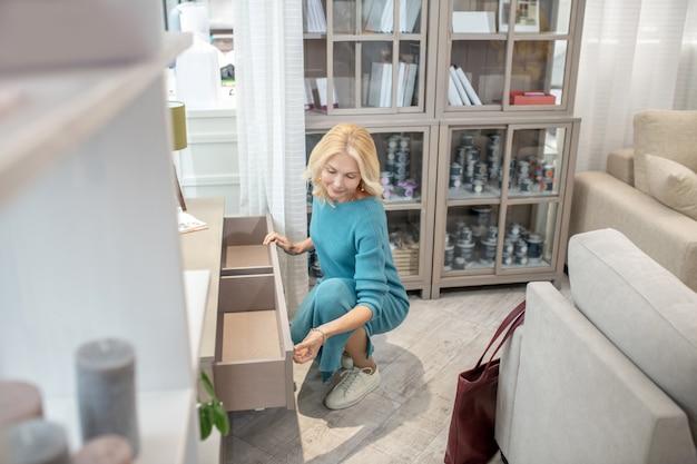 Jolie femme en robe bleue accroupie près d'un tiroir dans un salon de meubles, à la recherche de bonne humeur.