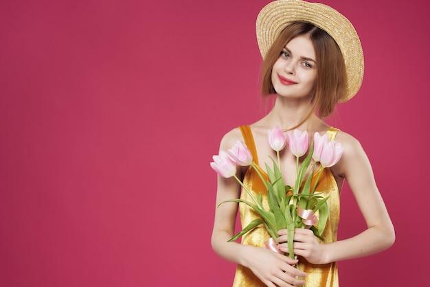 Jolie femme en robe avec bouquet de fleurs fond rose