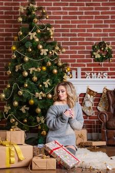 Jolie femme en robe chaude est assis sur un tapis de fourrure avec une tasse dans ses mains et regarde de côté près de l'arbre de noël et des cadeaux