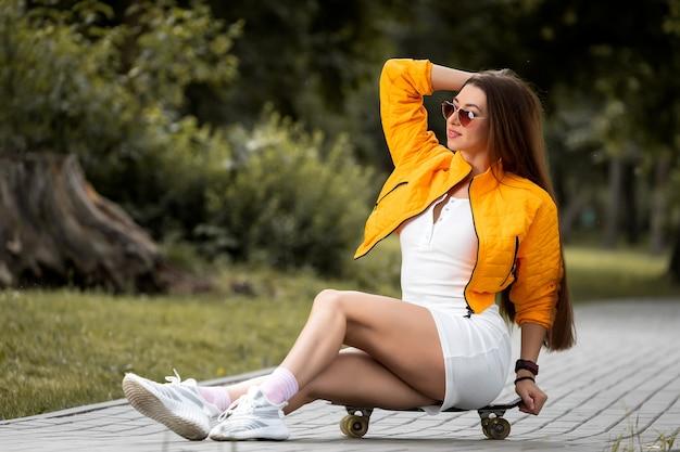 Jolie femme en robe courte assise sur la planche à roulettes et regardant loin en souriant tout en passant du temps au skate park. fille urbaine relaxante au skate park.