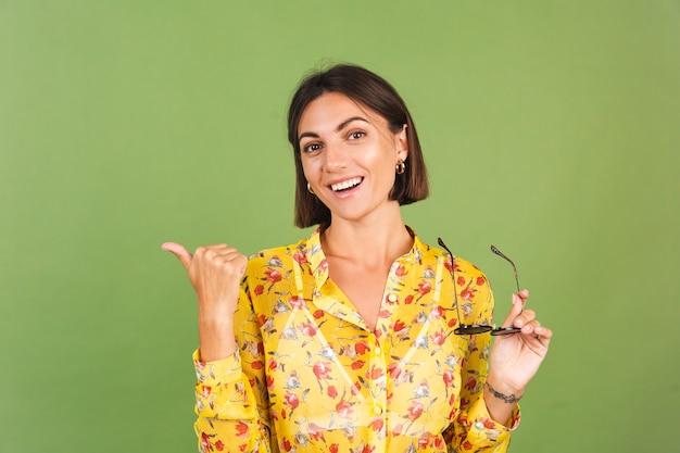 Jolie femme en robe d'été jaune et lunettes de soleil, studio vert, doigt pointé joyeux joyeux excité à gauche