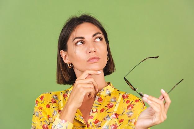 Jolie femme en robe d'été jaune et lunettes de soleil, studio vert, regard réfléchi de côté