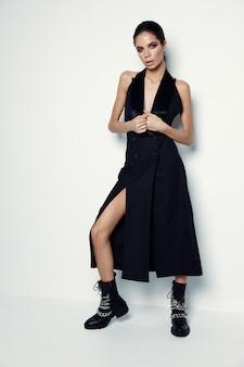 Jolie femme en robe noire et bottes modernes moda studio fond clair