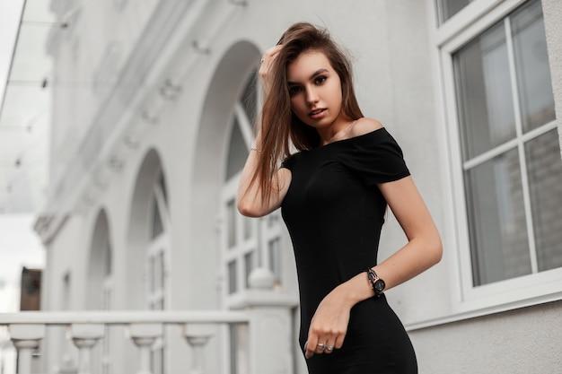 Jolie femme en robe noire se promène dans la ville