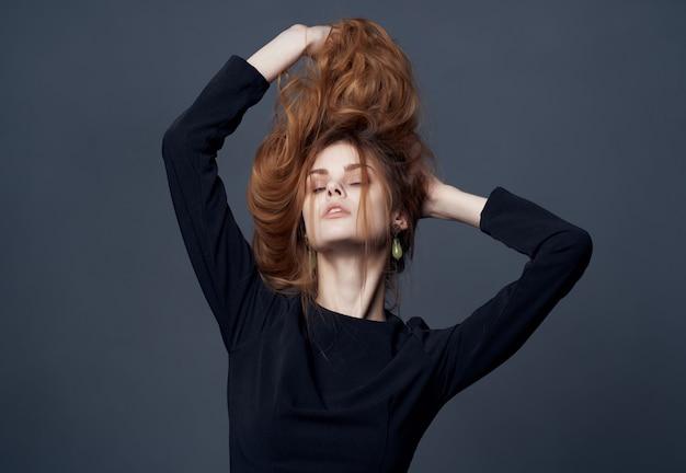 Jolie femme en robe noire tenant une coiffure fashion look attrayant