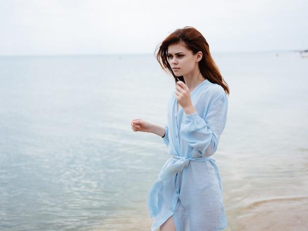 Jolie femme en robe par l'air frais de l'île à pied de l'océan
