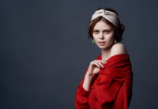 Jolie femme en robe rouge et cosmétiques de décoration de bandeau