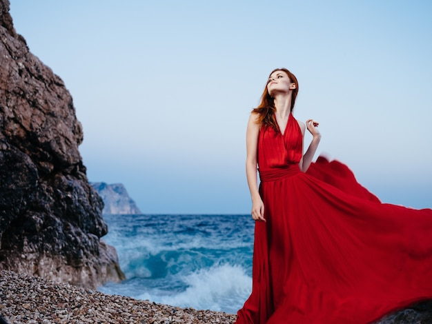 Jolie femme en robe rouge luxe posant fashion beach