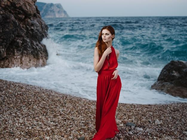 Jolie femme en robe rouge posant près de romance de vacances plage falaise