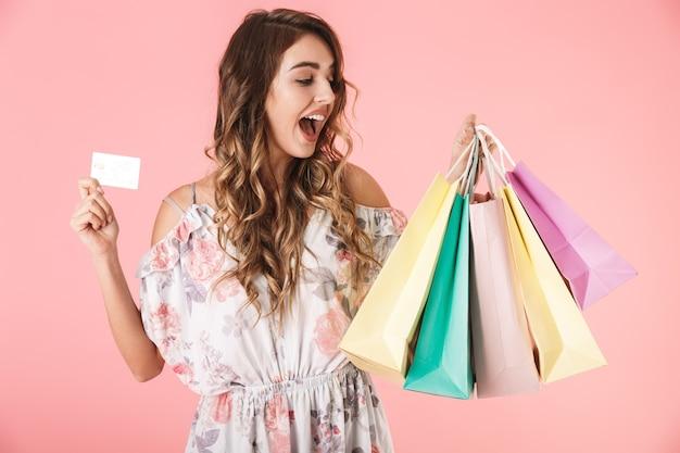 Jolie femme en robe tenant une carte de crédit et des sacs colorés, isolés sur rose