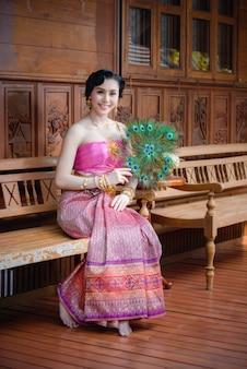 Jolie femme avec une robe thaïlandaise tenir fan de paon dans une vieille maison en bois thaï