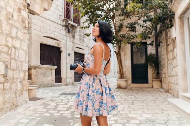 Jolie femme en robe treveling en vacances dans le vieux centre-ville de l'italie à prendre des photos à l'appareil photo