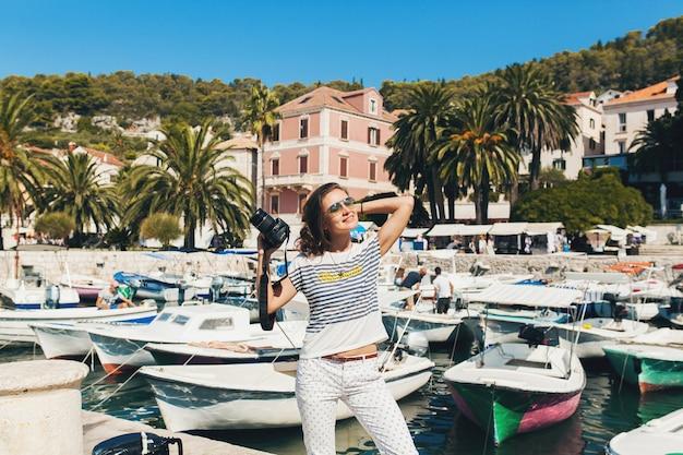 Jolie femme en robe treveling en vacances en europe au bord de la mer lors d'une croisière à prendre des photos à l'appareil photo