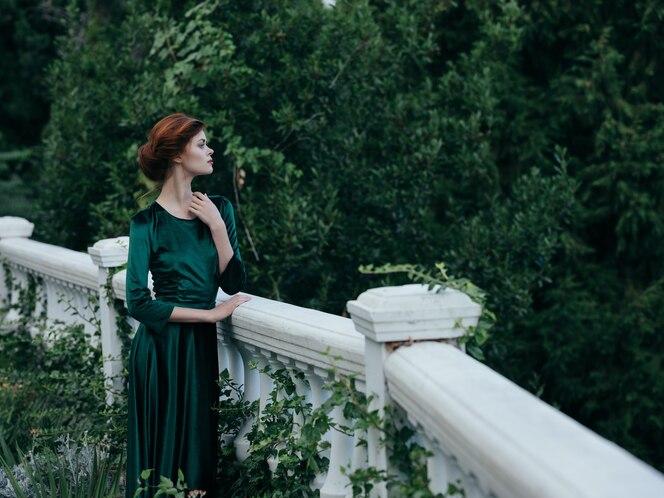 Jolie femme en robe verte à l'extérieur marchant dans la romance du parc