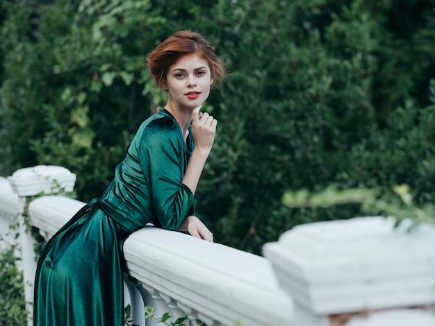 Jolie femme en robe verte nature romance marche glamour. photo de haute qualité