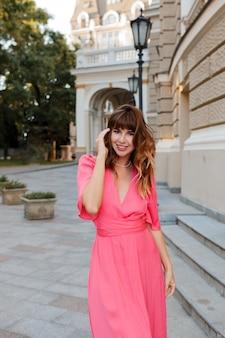 Jolie femme romantique en robe rose posant en plein air dans la vieille ville européenne.
