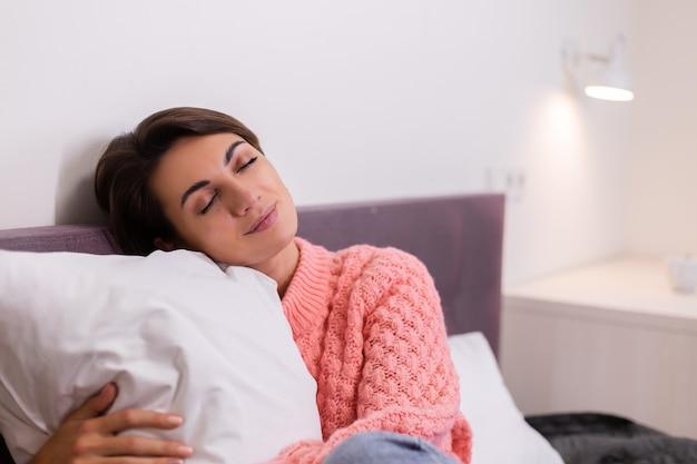 Jolie femme en rose pull tricoté mignon resing à la maison au lit, souriant, profitant du temps seul