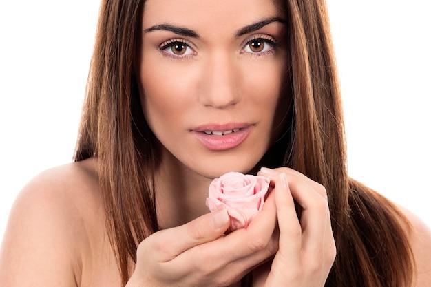 Jolie femme avec rose rose sur fond blanc