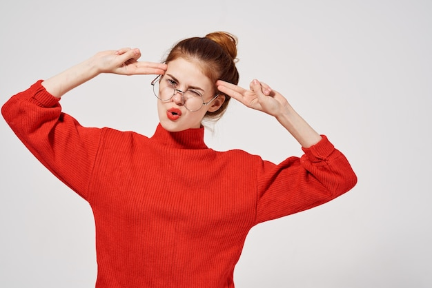 Jolie femme rouge pull main geste lunettes lèvres rouges fond isolé.