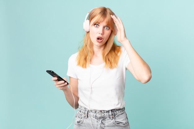 Jolie femme rousse ayant l'air heureuse, étonnée et surprise et écoutant de la musique avec des écouteurs