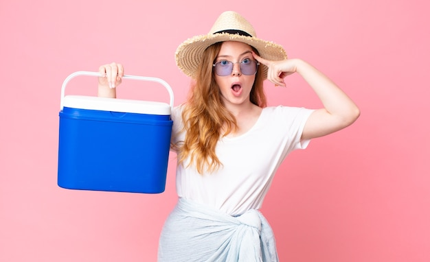Jolie femme rousse ayant l'air surprise, réalisant une nouvelle pensée, idée ou concept et tenant un réfrigérateur portable pique-nique