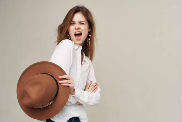 Jolie femme rousse en chemise blanche avec chapeau à la main style moderne de la mode. photo de haute qualité