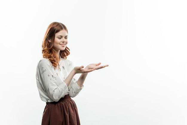 Jolie femme rousse en costume formel tient la main devant ses émotions fond clair amusant
