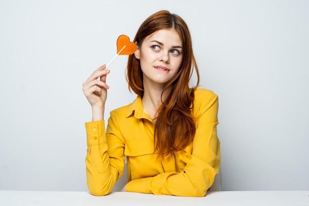 Jolie femme rousse dans une chemise jaune avec une sucette dans ses mains est assise à la table