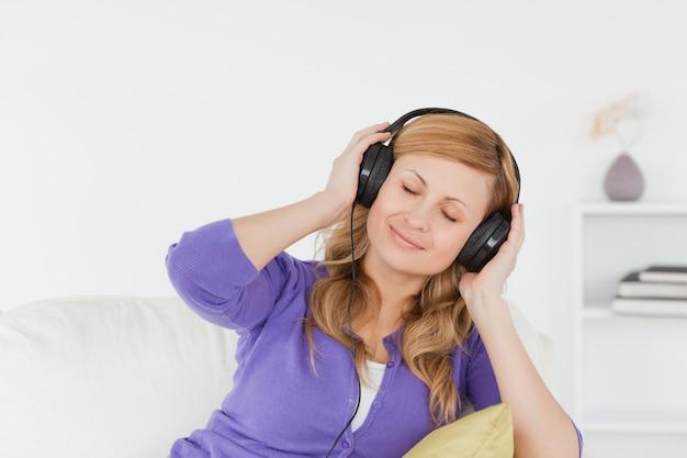 Jolie femme rousse, écouter de la musique et profiter de l'instant tout en étant assis sur un canapé