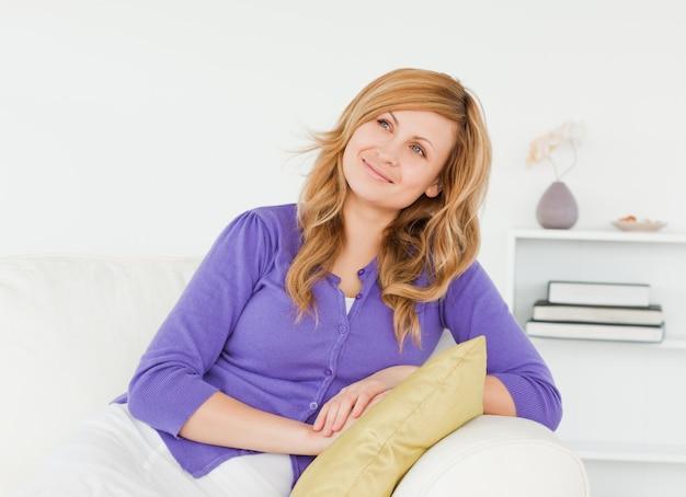 Jolie femme rousse avec un regard malveillant posant assis sur un canapé