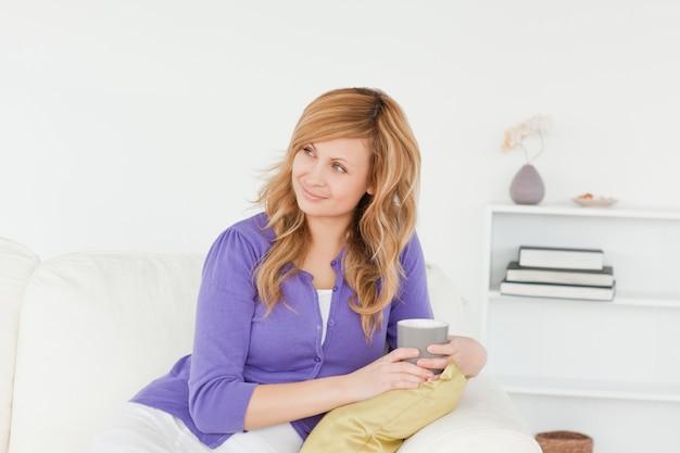 Jolie femme rousse regardant quelque chose assis sur un canapé