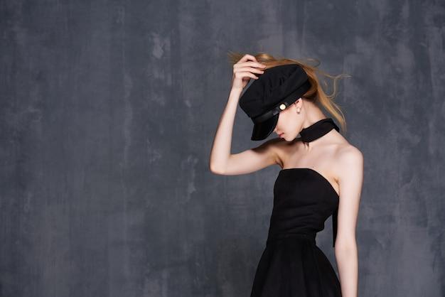 Jolie femme rousse en robe noire basant la mode de vie