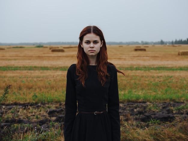 Jolie femme rousse en robe noire en mode voyage sur le terrain