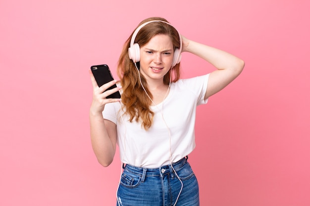 Jolie femme rousse se sentant stressée, anxieuse ou effrayée, les mains sur la tête avec des écouteurs et un smartphone