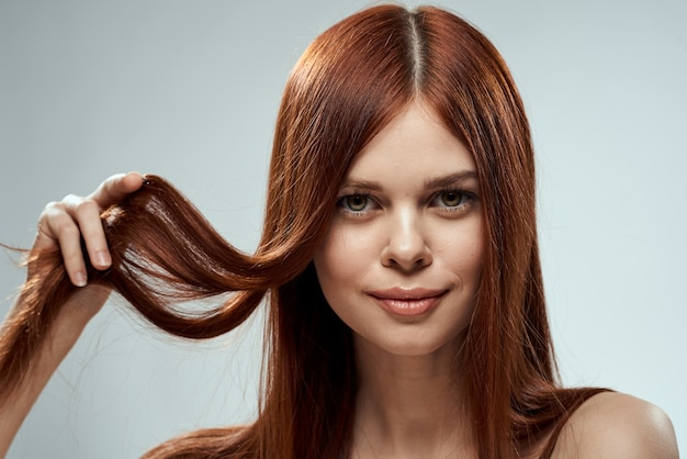 Jolie femme rousse tenant ses cheveux avec les mains toilettage des épaules nues espace léger.