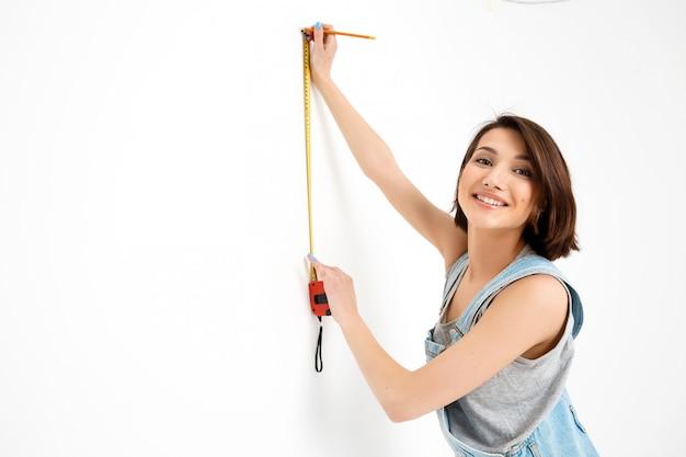 Jolie femme avec ruban à mesurer rénover la maison