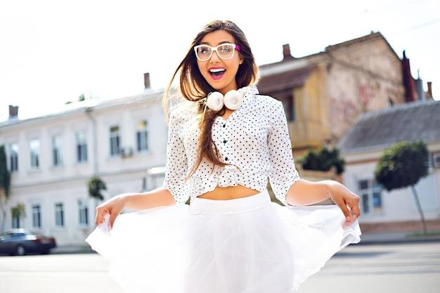Jolie femme s'amusant dans la rue, portant une robe drôle blanche et un casque blanc