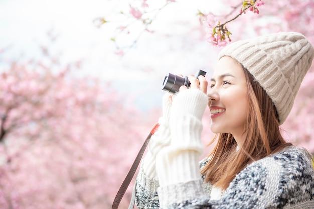 Jolie femme s'amuse avec des fleurs de cerisier à matsuda, japon