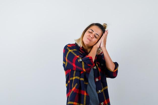 Jolie femme s'appuyant sur les paumes comme oreiller dans des vêtements décontractés et ayant l'air endormi