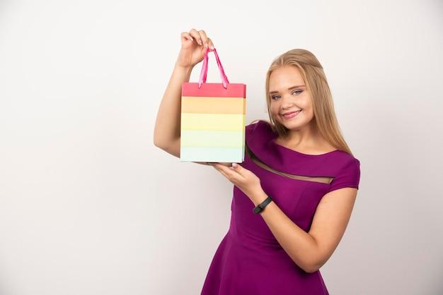 Jolie femme avec sac cadeau posant. photo de haute qualité