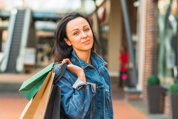 Jolie femme avec des sacs dans un centre commercial
