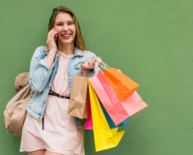 Jolie femme avec des sacs à provisions lumineux parlant par téléphone