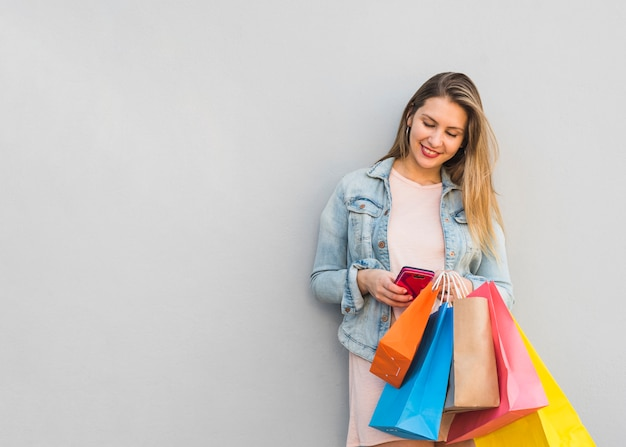 Jolie femme avec des sacs à provisions en utilisant un smartphone